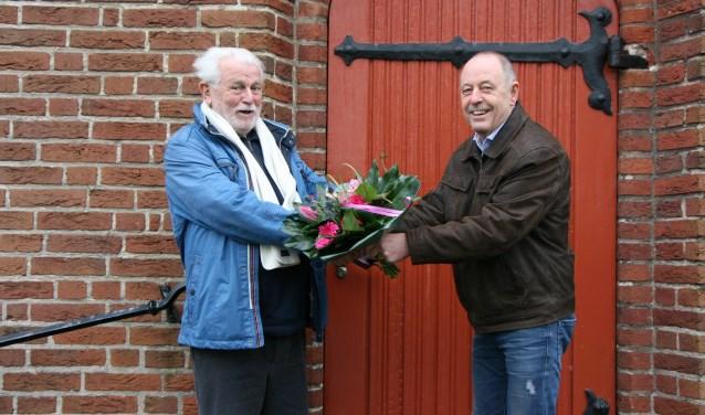 Jan Roelofs overhandigt pastor Visschedijk een boeket bloemen namens het parochiebestuur.