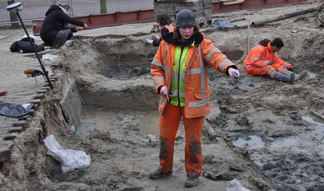 Els Coppens van erfgoedadviesbureau Artefact legt uit dat de botresten op de verschillende vindplaatsen ook in een andere richting begraven lagen. Achter haar Constance van der Linde en Dante de Ruijsscher.