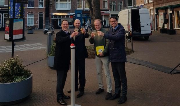 Boudewijn Revis (l), Bas Winkler (midden-links, BIZ), Jan van Eijk (midden-rechts, BIZ) en Karsten Klein (r) hebben met een gezamenlijke druk op de knop de lichtjes in de zes bomen op het Torenplein ontstoken. (Foto: gemeente Den Haag)
