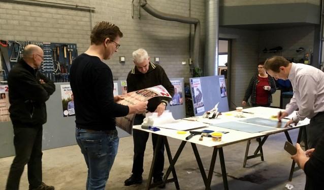 Medewerkers van de vier politieke partijen in Haaren, Samenwerking 95, VVD, CDA en Progressief 96 plakken posters van hun partijen op borden die deze week in de vier dorpen worden geplaatst. De campagne voor de gemeenteraadsverkiezingen op 21 maart kan beginnen.