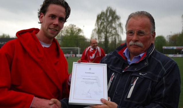 Van Dijk (links) krijgt een KNVB-certificaat ter gelegenheid van kampioenschap en promotie. Foto: Gerard van Vliet.