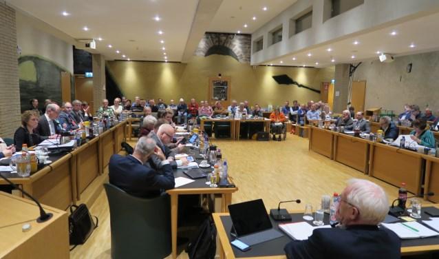 Een volle publieke tribune volgt het debat in de raad over het scherm. (foto GvS)