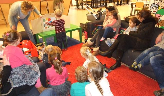 Kinderen en ouders luisteren aandachtig naar het verhaal van Britta Teckentrup.
