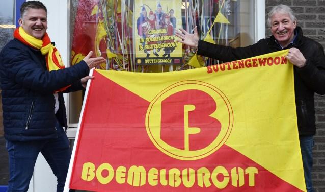Marc van den Boom (links) van de Stichting Vrienden van Carnaval in Boemelburg toont de rood-gele Boemelburchtvlag samen met centrummanager Ton van Lier. Op de achtergrond de etalageversiering die in 47 winkels komt te hangen. (foto: Ab Hendriks)