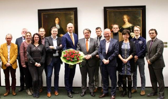 Marcel Fränzel (midden met bloemen), cdK Wim van de Donk, fractievoorzitters en college van Oosterhout