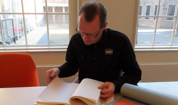 Gerard van den Houten verdiept in archiefstukken. Hij wil een mooi, dik boek maken over FC Dordrecht. (foto: Elisa Kuster)