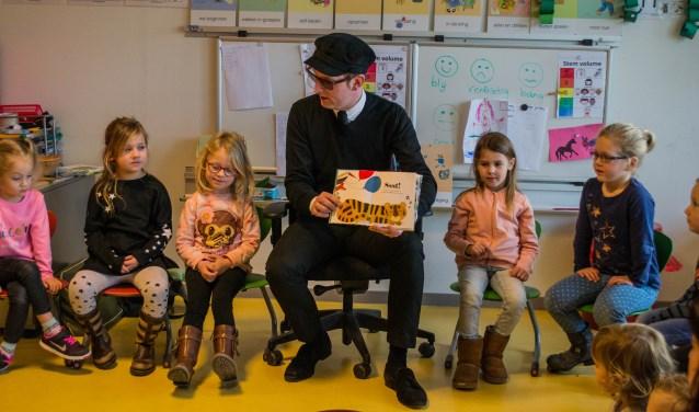 The Kik-zanger Dave von Raven leest voor aan groep 1 en 2 van obs de Regenboog en de kindjes van Kibeo in Ooltgensplaat. FOTO: Sam Fish