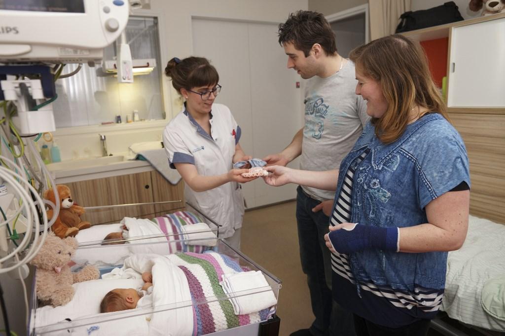 Verpleegkundige Mirjam overhandigt de ouders van Xander en Amanda twee feestmutsjes.  © Persgroep
