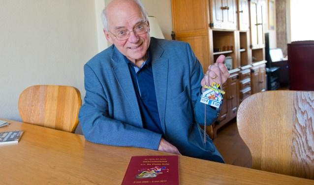 Vol trots toont Gerard Jansen, de voorzitter van CV De Platte Knip, de onderscheiding die speciaal voor dit jubileumjaar is ontworpen. (Foto: Maaike van Helmond)