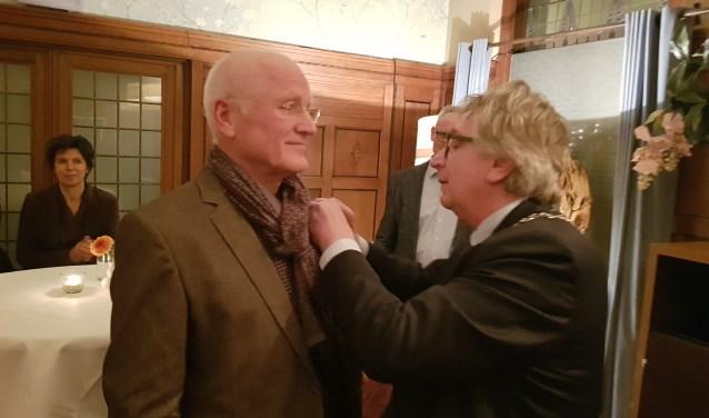 Burgemeester Geert van Rumund speldt Tom Kool het Wagenings Erezilver op vanwege diens verdiensten voor de stad. (foto: Kees Stap)