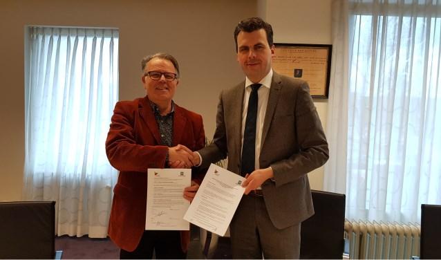 De wethouders Harry van de Ven (links) en Berend de Vries (rechts) schudden elkaar hand na ondertekening van het contract.
