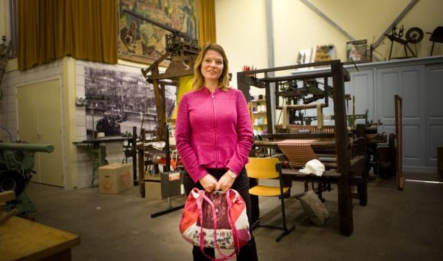 Kunstenaar en kostuumontwerper Ine Keitz in de Museumfabriek met een tas uit haar collectie