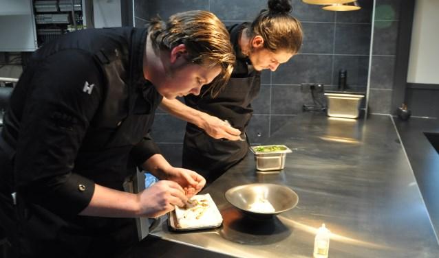 Rechts chef-kok Michael van der Kroft, links Jeroen Hoep junior, bezig met de bereiding van inktvisnoedels met cantharellen. FOTO: Anneke Flikweert