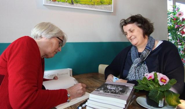 Schrijfster Lida van de Voorde signeert het boek 'zelf gemaakt geluk'. Anja van Rookhuijzen is benieuwd naar de inhoud van de roman en heeft zich voorgenomen nog dezelfde avond aan het boek te beginnen. (foto: Kirsten den Boef)