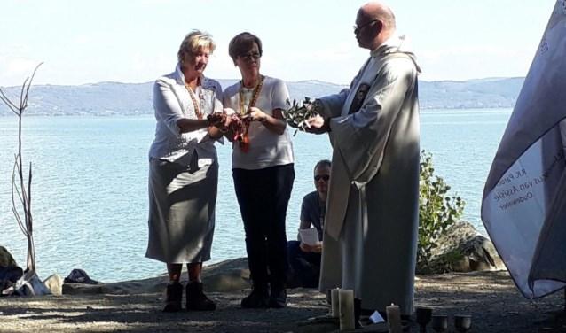 """Anneke van den Hadelkamp en Grada Nederhof met pastor Spaan tijdens de bijzondere eucharistieviering aan het meer in Italië. ''Toen we daar in de voetsporen van Franciscus van Assisi traden, raakte zijn bijzondere manier van leven nog meer."""" (Foto: Anneke van den Hadelkamp)"""