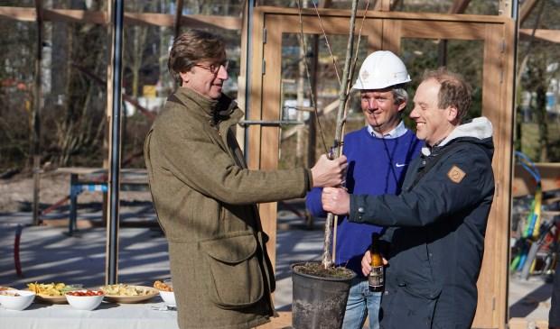 Benno Smit van de Wijkvereniging Belgisch Park feliciteert de initiatiefnemers Robert-Jan Vermeulen en Wessel Tiessens met het bereiken van het hoogste punt en overhandigt namens de buurt de eerste fruitboom voor de zorg(moes)tuin van Greens.