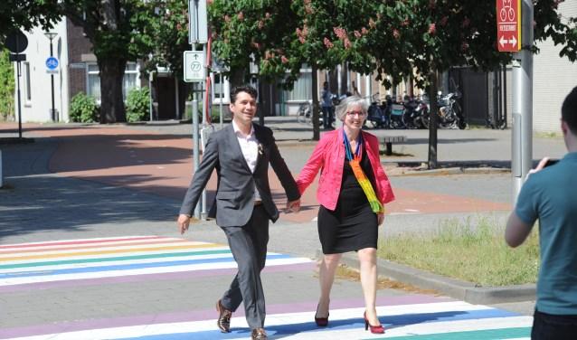 Wethouders Eric Logister van Den Bosch en Annemieke van de Ven van Oss, hand in hand over het 'gaybrapad' in Oss.