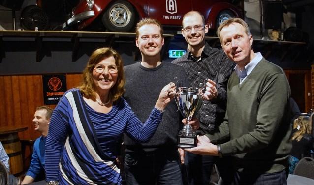 Winnaars van De Grote Twijn Pub Quiz poseren trots met beker.