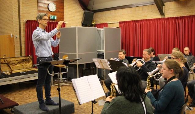Hendry van Loo dirigeert het fanfare-orkest van ULTO. Samen repeteren ze voor het concert op 8 april.