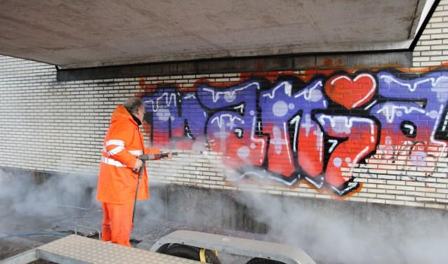 Met een hogedrukspuit wordt graffiti verwijderd uit een tunneltje. Foto: PR