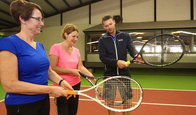 Mariëtte Selman (links) en Angelien Marcelis uit Elst krijgen uitleg van voormalig tennistopper Sjeng Schalken. Hij geeft in de Schaapskooi in Bemmel een speciale clinic waarvoor zich tachtig deelnemers hebben gemeld. (foto: Kirsten den Boef)