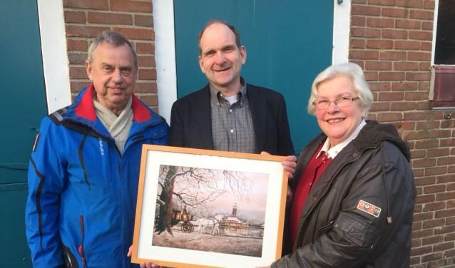 Jopie Nellestein overhandigt het schilderij aan Karel Heij van Drukkerij Modern. Pieter Oosterveld, voorzitter van de Manege zonder Drempels, kijkt toe. (foto: Anja van Velsen)