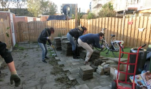 Vrijwilligers van Stichting Present Walcheren helpen in een tuin om die begaanbaar te maken voor een scootmobiel. Foto: Conny den Heijer