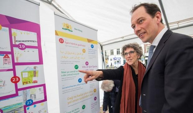 Wethouder Boudewijn Revis bekijkt samen met initiatiefneemster Ingrid Tieken uit de Stationsbuurt de spreuken en de bijbehorende tekeningen van de Jan Ligthartschool. (fotograaf: Arnoud Roelofz)