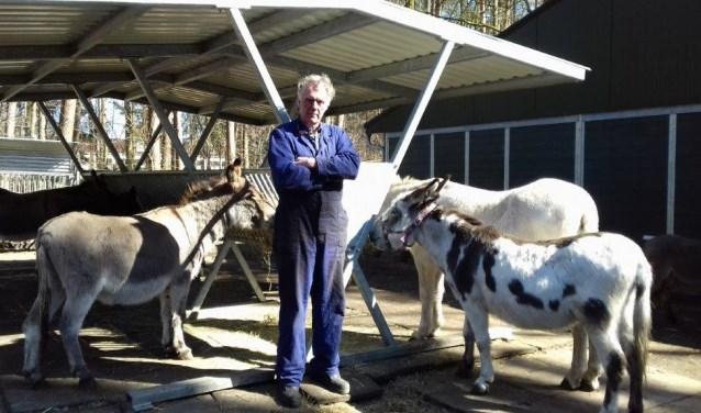 Mens en ezel, zijn gelukkig met de nieuwe overdekte hooiruif,. De ruif is gesponsord door Stichting Dierenwelzijn,