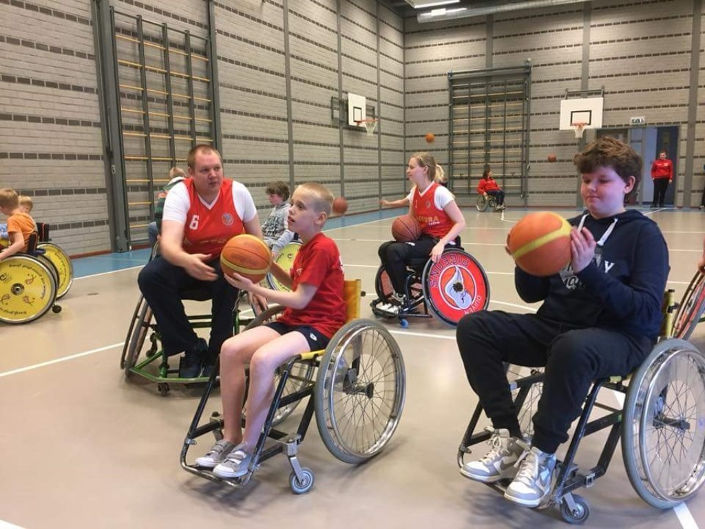 Martijn en Isabelle Pigeons On Wheels en twee kinderen die kennis maken met rolstoelbasketbal.