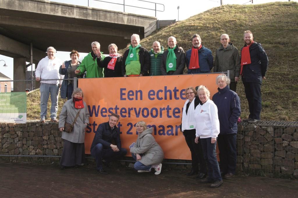 De radiomakers van 'Spraakmakers' en vertegenwoordigers van de politieke partijen in Westervoort bij het spandoek dat vrijdag werd onthuld bij het spoorviaduct in het dorp.