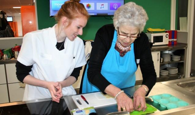Wendela gaf een kookworkshop aan diverse vrijwilligers van de Zonnebloem afdeling Putten. Ze legt aan mevrouw Willemsen uit wat precies de bedoeling is. Foto: Annemieke Westphal-Kreeftmeijer