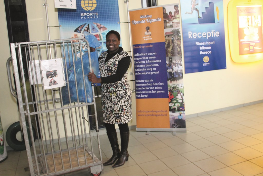 """Pauline Ukumu met de kledingcontainer in Sports Planet: """"Ik was in 2008 voor het eerst terug in Oeganda en werd er getroffen door het leed dat veel kinderen treft."""""""
