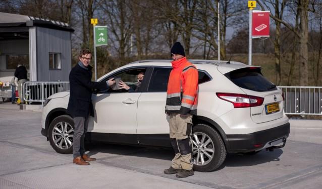 Wethouder Jan Overweg gaf de eerste bezoekers van de vernieuwde Milieustraat een 'milieuvriendelijke' attentie: een afvalbakje. (Foto: Hetty Heijne)