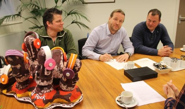 Voorzitter Niels Kuenen van de Wooldse Corsoclub tekent de akte terwijl secretaris Leon Kamperman (rechts) en bestuurslid Reinoud Hoijtink (links) toekijken. Links de maquette van de nieuwe corsocreatie 'Hardrock'.