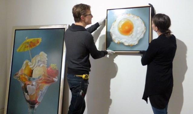 Michael Klinkenberg en Karin van Lieverloo hangen samen het Cunen-ei op. Dat kunstwerk is, samen met de andere kunstwerken bij 'We Are Food - Over de kunst van voedsel' is tot met zondag 16 september te zien bij Museum Jan Cunen.