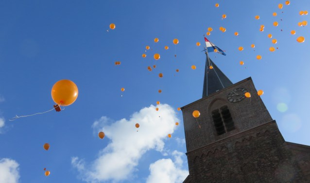 Koningsdag in Bennekom start traditiegetrouw met het oplaten van oranje ballonnen.