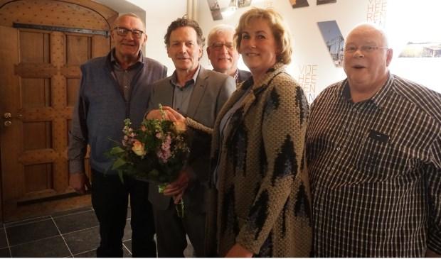 Teus Meijdam krijgt bloemen van bestuursvoorzitter Caroline Schouten, omringd door de fractievoorzitters. Hans van de Berg ontbreekt op de foto en wordt vervangen door Henk Heijltjes.