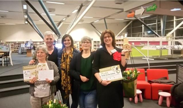 De winnaars van de 'heldere taal'-prijzen Yvonne de Heer-Seveke van TROTS Breda en Miriam Haagh van de PvdA gingen in de Bredase bibliotheek samen op de foto met het testpanel. FOTO: ERNESTINE SCHIPPER