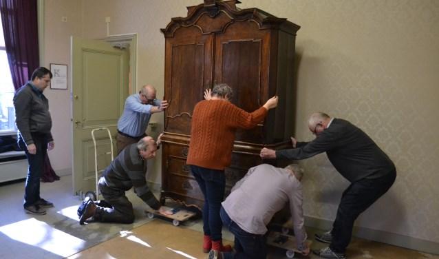 Bij het vervangen van het tapijt moet alles van de plaats, zoals dit antieke kabinet dat met de nodige voorzichtigheid aangepakt moet worden. Foto: Jan Joost.