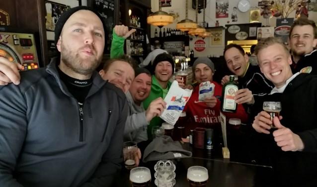De uitgelaten groep schaatsers uit Wateringen aan het bier, de ijsmoppen en de fles Jägermeister in bierlokaal Antonius op de Hoogstraat.