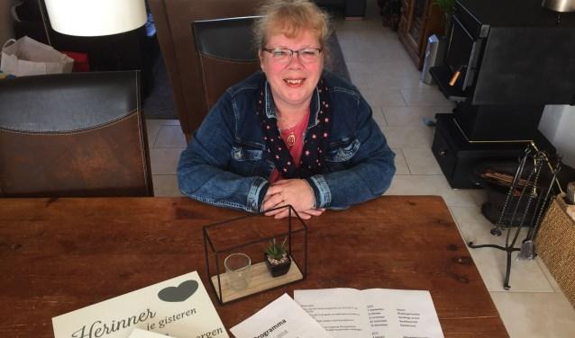 Voorzitter van KVO'80 Carla de Roos toont een gewonnen prijs met de loterij, de programmaboekjes en twee borden met spreuken die zij maakte tijdens een creatieve avond.