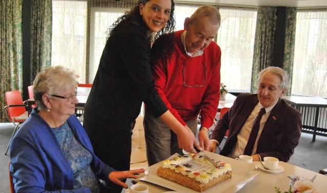 Dyanne Pinas en de heer Van den Berg snijden de taart aan.