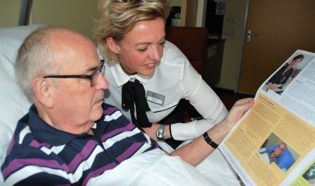 Bewoner Mar Langbroek van hospice De Cirkel leest onder toeziend oog van coördinator Ester Pos trots zijn interview in de jaarkrant 2018.