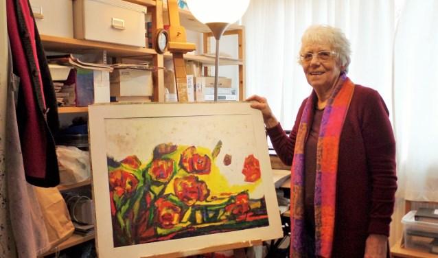 """Corry Scholten in haar atelier bij een schilderij in wording. Zij begint vaak gewoon te schilderen en abstraheert de voorstelling dan steeds verder. """"Schilderen is veel kijken naar het effect van de verf en wat wel en niet werkt."""" Soms gebruikt zij een foto als inspiratie. (Foto: Anja Helmink)"""