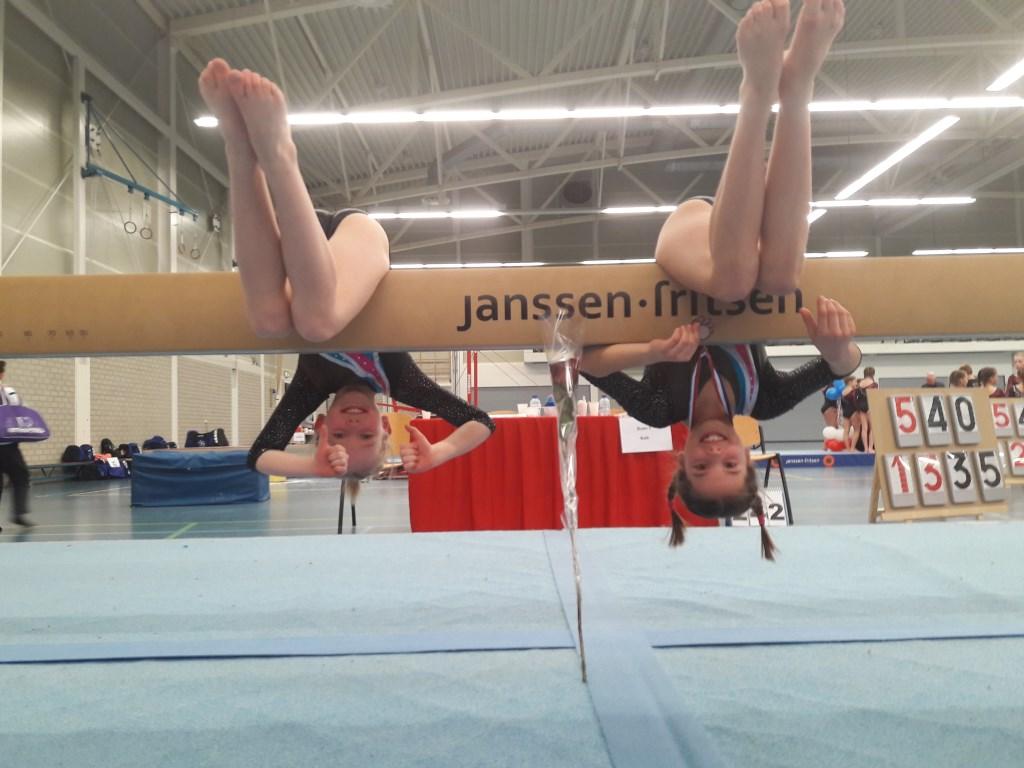 Turnsters hangend onder de balk - v.l.n.r. Jente Belt en Liessel Mureau  © Persgroep