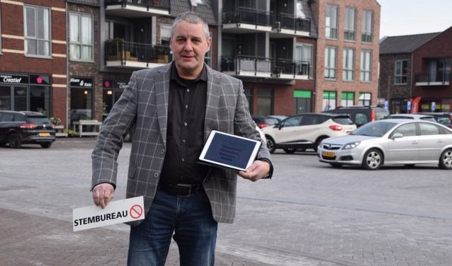 Erik Peters met het bordje dat verwijst naar zijn tijdelijke werkplek: woensdag 21 maart neemt hij weer zitting achter de tafel van het stembureau in Dreumel. (Foto Hanneke Hoefnagel)