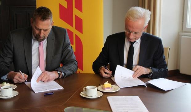 Burgemeester Hans Verheijen (rechts) en CEO DHL Supply Chain Benelux John Scherders ondertekenen het contract voor de kavelverkoop.