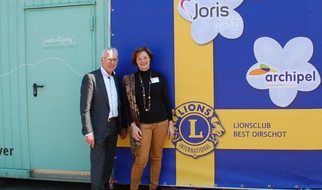 Harry Jannink, president van Lions Best Oirschot, en Diana Engels, voorzitter Raad van Bestuur Joris Zorg poseren bij de simulatiecabine Into D'mentia.