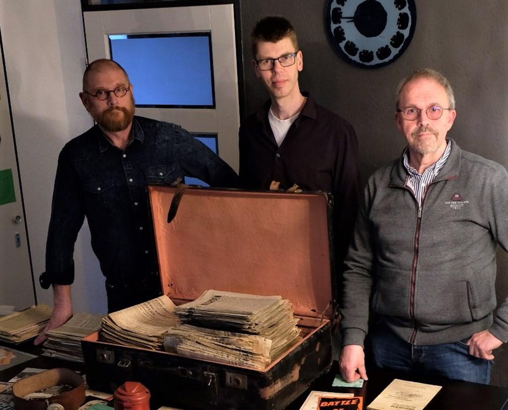 De broers Honoré (links) en Raymond de Beer met de bijzondere koffer. In het midden de verheugde ontvanger Eric Heijink, beheerder van de collectie Enschede in WOII. Foto: Herman Wolters
